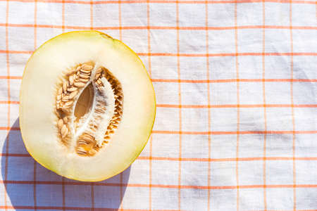 Cut yellow melon on a tablecloth. Top view, flat lay.