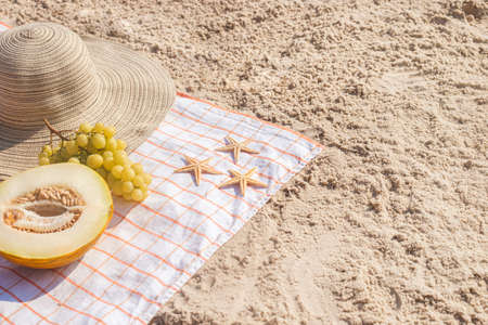 Half a melon, grapes, starfish on the beach. Top view, flat lay.