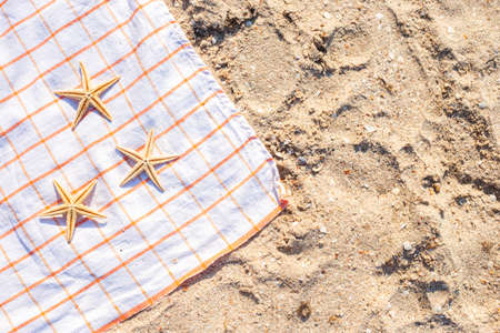 Golden starfish on a bedspread on a sandy beach. Top view, flat lay.