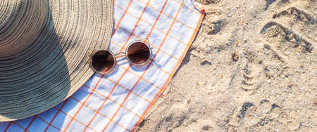Women's hat, glasses on the sandy beach. Top view, flat lay. Banner.