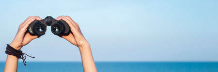Female hands hold binoculars against the background of the sky and the sea. Banner. Фото со стока