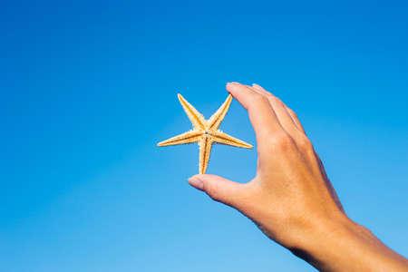 Female hand holds a starfish against the blue sky Фото со стока