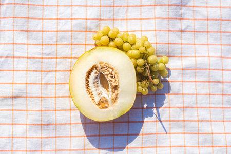 Cut yellow melon, grapes on a tablecloth on the beach. Top view, flat lay. Фото со стока