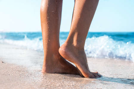 Female feet stand on tiptoes on a sandy beach on a summer day.