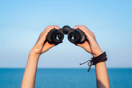 Female hands hold binoculars against the background of the sky and the sea.