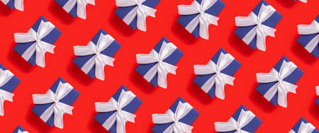 Lots of Christmas gift boxes blue with a white ribbon on a red background. Top view, flat lay. Banner.