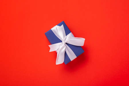 Gift blue with a white ribbon on a red background. Top view, flat lay.
