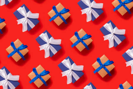 Lots of Christmas gift boxes on a red background. Top view, flat lay. Фото со стока