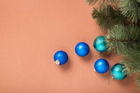 Fir branches and Christmas tree decorations on a brown background. Concept for New Years and Christmas Eve. Banner. Фото со стока