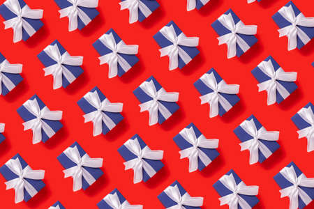 Lots of Christmas gift boxes blue with a white ribbon on a red background. Top view, flat lay.
