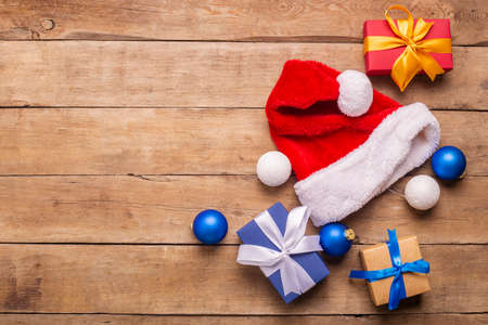 Santa Claus hat and gifts on a wooden background. Concept for Christmas, New Year. Top view, flat lay.