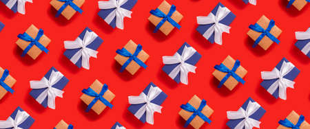 Lots of Christmas gift boxes on a red background. Top view, flat lay. Banner. Фото со стока