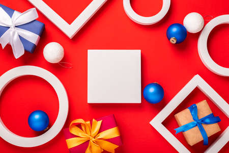 Podium, gifts and Christmas toys on a red background. Top view, flat lay.