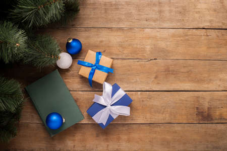 Gifts and Christmas decorations under the Christmas tree on a wooden background. Banner. Flat lay, top view.