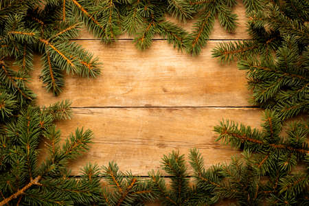 Wooden wall with Christmas tree branches. Christmas concept. Banner. Copy space.