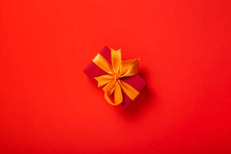 Red gift with orange ribbon on a red background. Top view, flat lay. Фото со стока