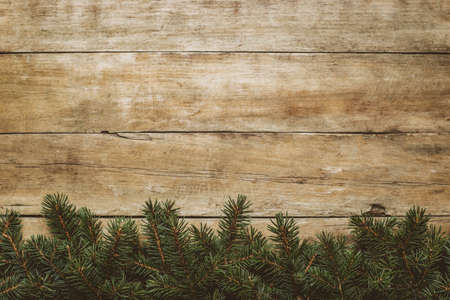 Wooden background with Christmas tree branches and snow. Christmas concept. Banner. Flat lay, top view.