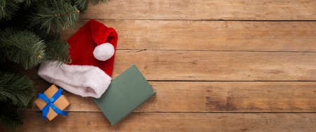 Book and hat of Santa Claus on a wooden background. Top view, flat lay. Banner. Фото со стока