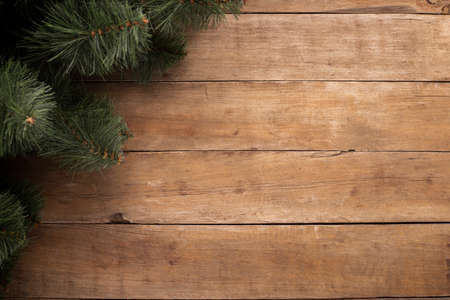 Wooden background with branches of a Christmas tree. Concept for Christmas and New Year. Banner. Flat lay, top view.