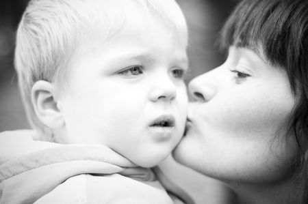civility: Mother kissing her baby. Stock Photo