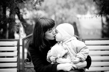 A young mother sitting on a park bench with her baby child in her arms. Stock Photo - 4340932
