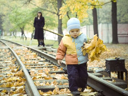 child with his mother in autumn park. mother blurred photo