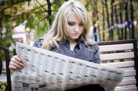 Joven mujer leyendo un diario mientras est� sentado en una banca del parque Foto de archivo - 4494345