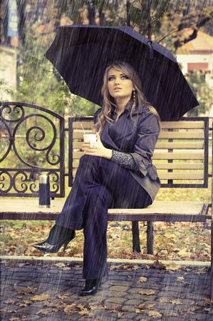 Girl with umbrella sitting on bench at autumn park. its raining photo