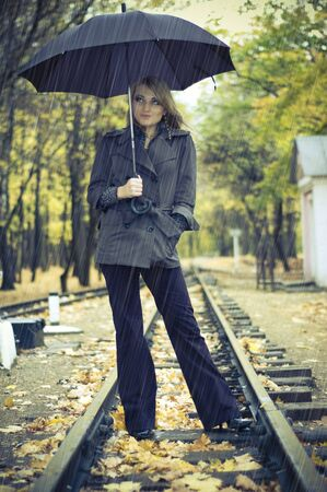beautiful woman with blond long hair at autumn park. it's raining Stock Photo - 4651870