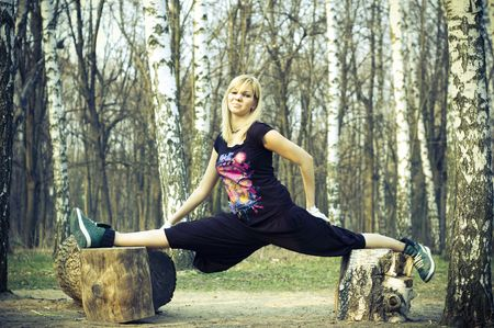 blond girl in the forest. Girl in splits. photo