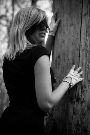 girl blindfolded beside a tree photo