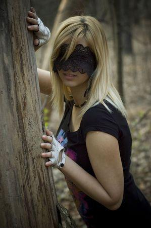 blindfolded: girl blindfolded beside a tree