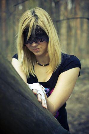 ojos vendados: chica con los ojos vendada al lado de un árbol