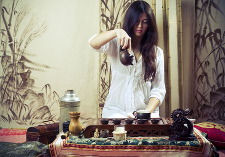 A young girl holds a Chinese tea ceremony photo