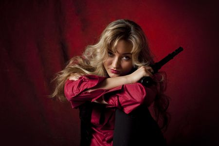 portrait of a young girl in a red shirt with a gun Stock Photo - 6900667