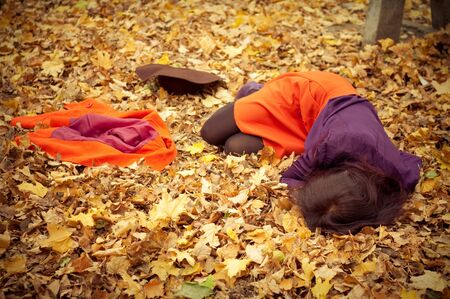 girl in the forest: girl lies among the fallen yellow leaves Stock Photo