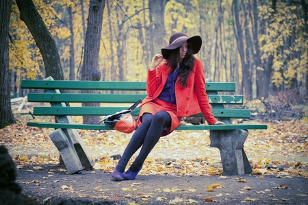 girl sitting on a park bench in late autumn photo