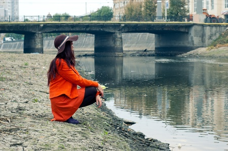 velours: girl in a hat sits on the banks of the river