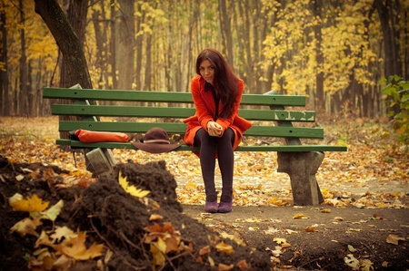 girl sitting on a park bench in late autumn Stock Photo - 11800268