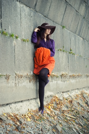 �aucasian: stylish girl lying on a stone wall