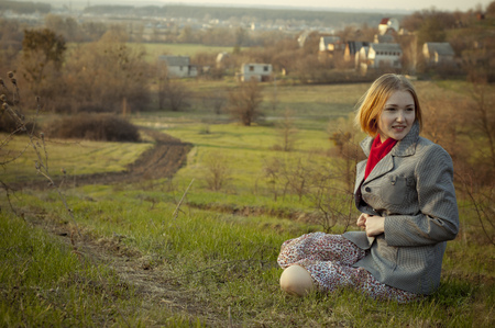 Beautiful girl sits on the background of the rural landscape  photo