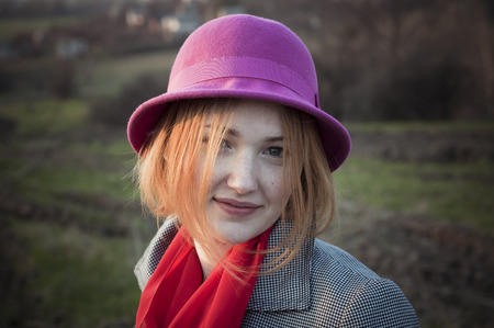 Close-up portrait of a smiling girl in a pink felt hat. photo
