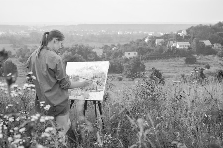 plein: Black-and-white photography of a young girl-artist painting with watercolor on the plein Air Stock Photo