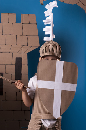 photo of the boy in medieval knight costume made of cardboards. this decorations are made specially for this photosession by me. Stock Photo