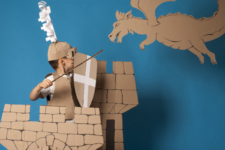 specially: photo of the boy in medieval knight costume made of cardboards. this decorations are made specially for this photosession by me. Stock Photo