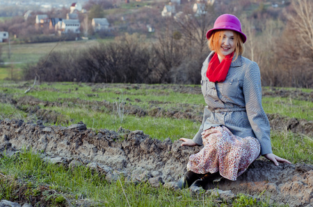 Beautiful girl sits on the background of the rural landscape. photo
