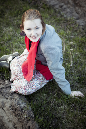 Beautiful girl in a red scarf sitting on the ground. photo