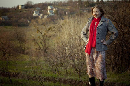 Beautiful young girl in red scarf. Rural landscape is on the background. photo