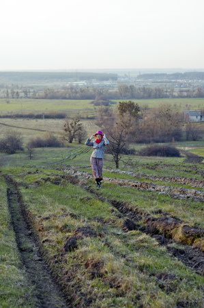 Young girl goes through the plowing. Rural landscape on the background. photo