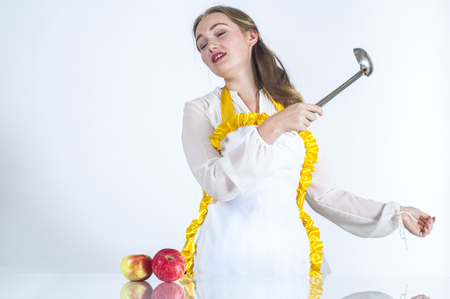 homemaker: Photo of dreaming homemaker in kitchen on white background.